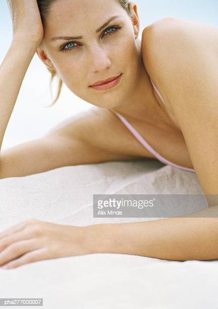 Young woman lying on sand, leaning on elbow, looking at camera