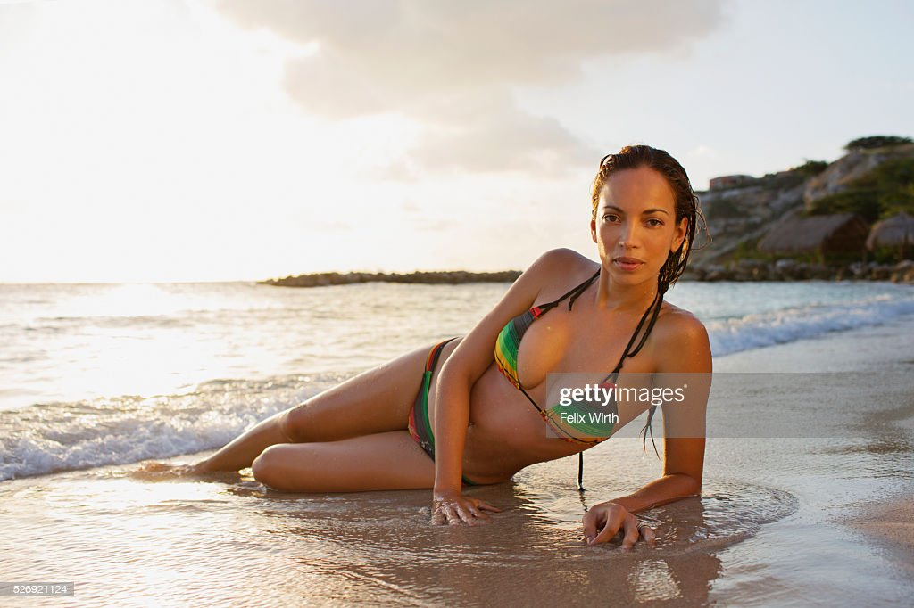 Young woman lying on sand on tropical beach : Bildbanksbilder
