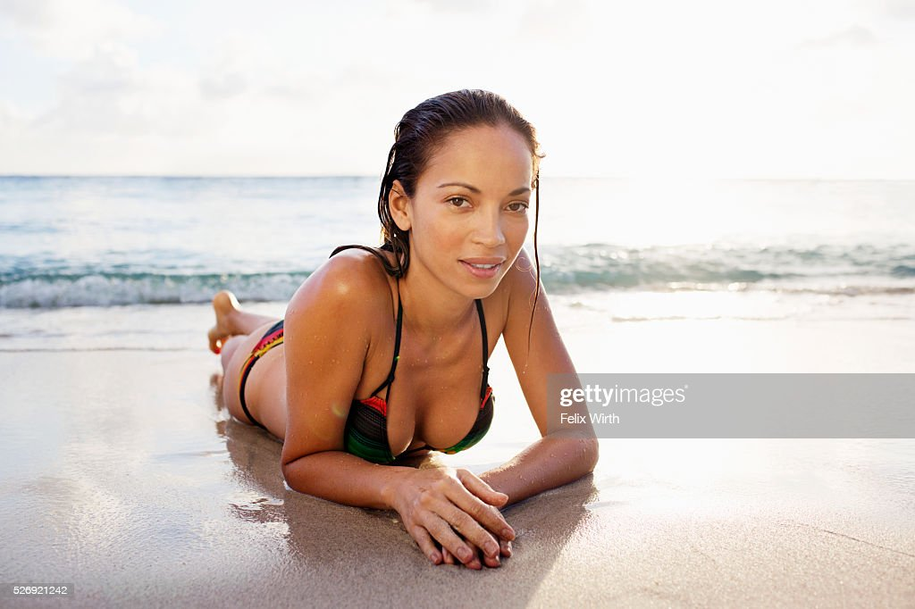 Young woman lying on sand on tropical beach : Stock Photo