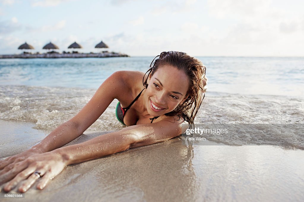 Young woman lying on sand on tropical beach : Stock-Foto