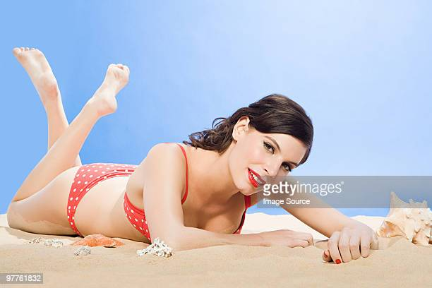 Young woman lying on sand