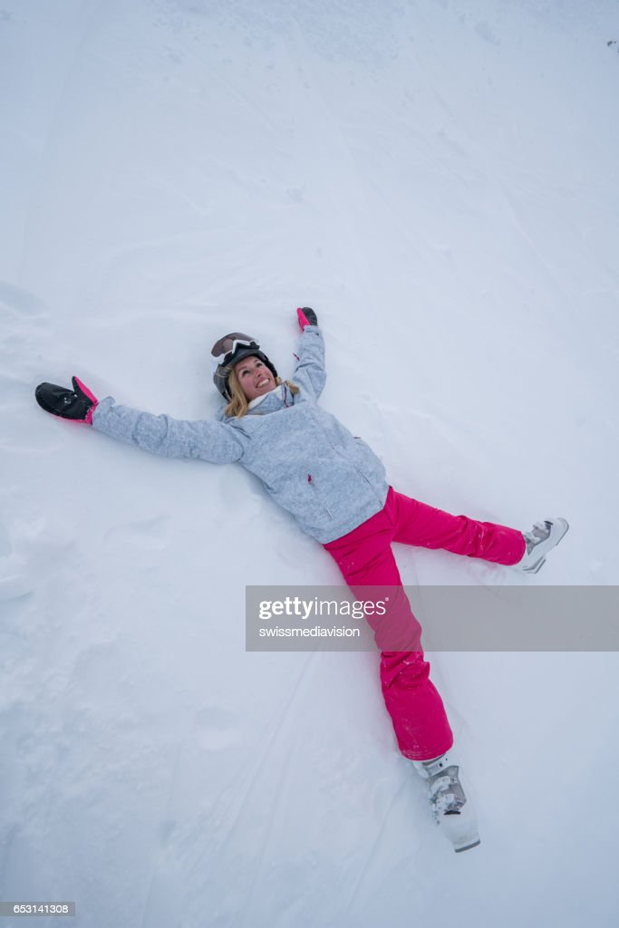 Young woman lying on snow playing snow angel : Stock Photo
