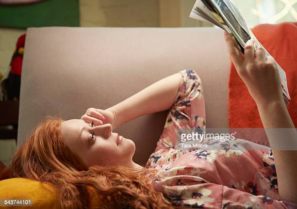 young woman lying on sofa at home reading magazine - magazine stock pictures, royalty-free photos & images