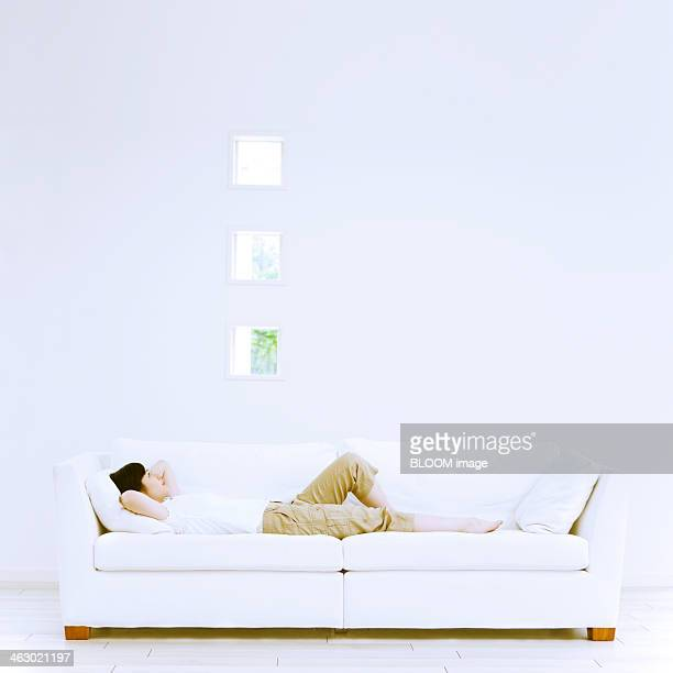 young woman lying on sofa - tidy room stock pictures, royalty-free photos & images