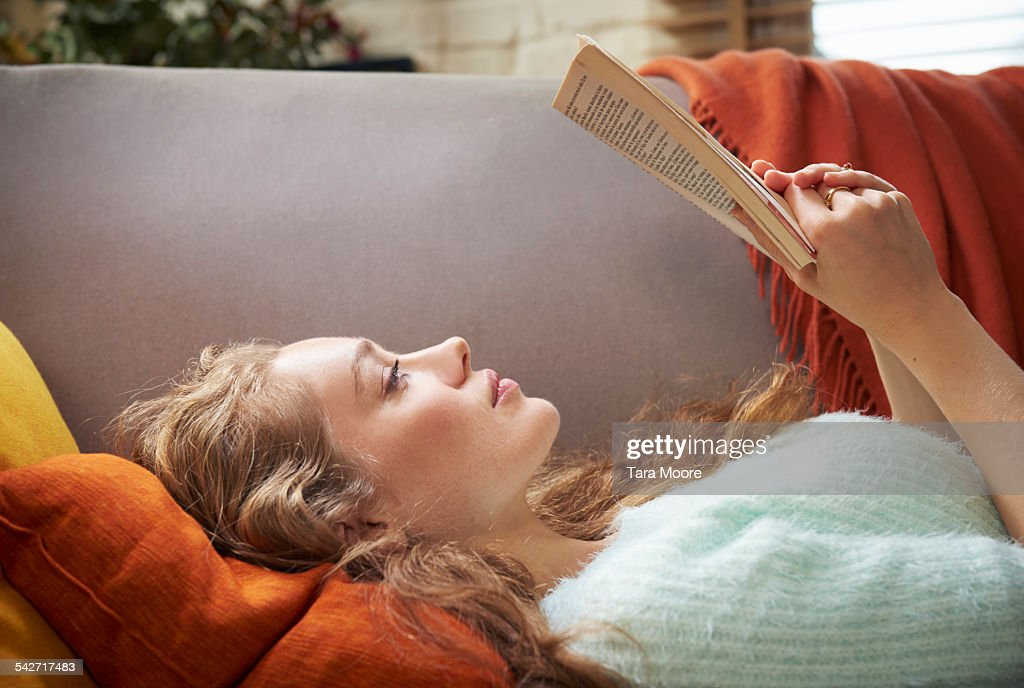 Young woman lying on sofa reading : Stock Photo