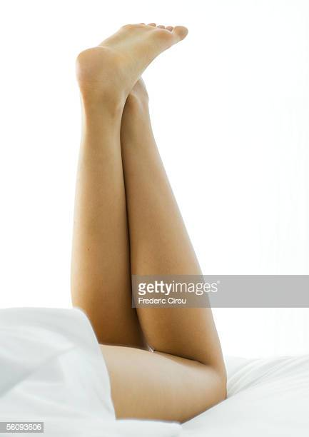 Young woman lying on stomach with legs up