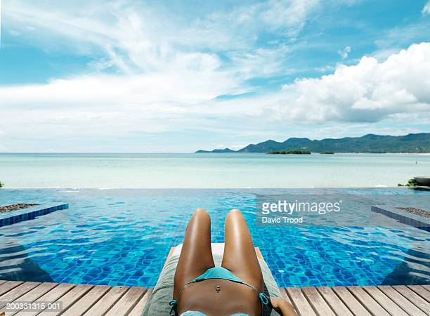 Young woman lying on sun lounger by infinity pool, low section
