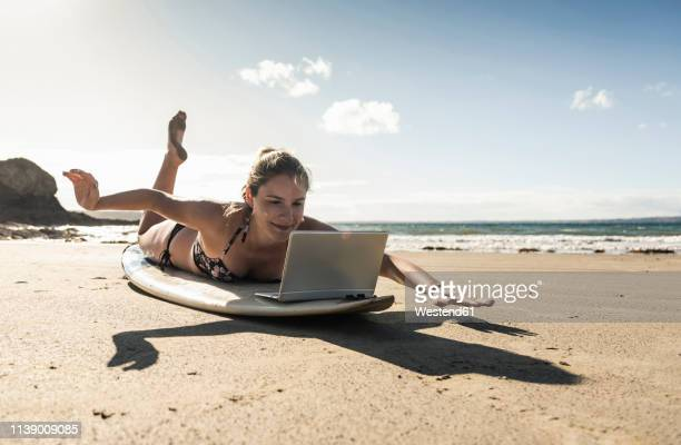 young woman lying  on surfboard, using laptop - tutorial stock pictures, royalty-free photos & images
