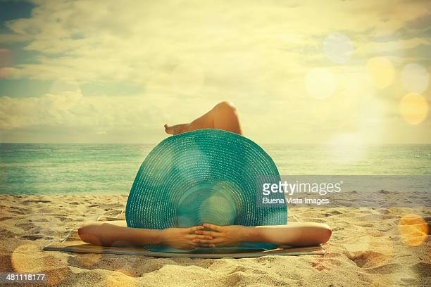 young woman lying on the beach - sun hat stock pictures, royalty-free photos & images