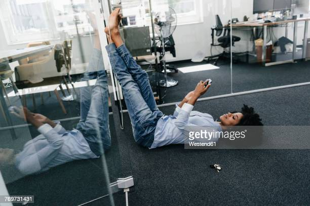 Young woman lying on the floor in office checking cell phone