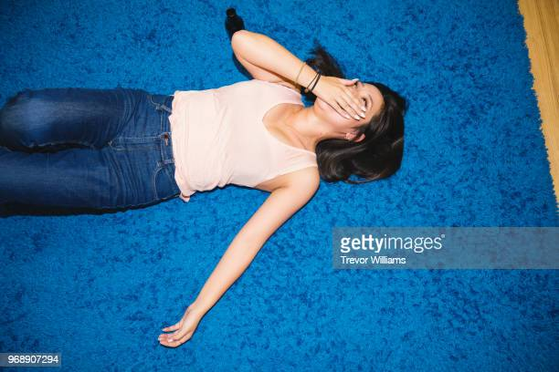 Young woman lying on the floor laughing