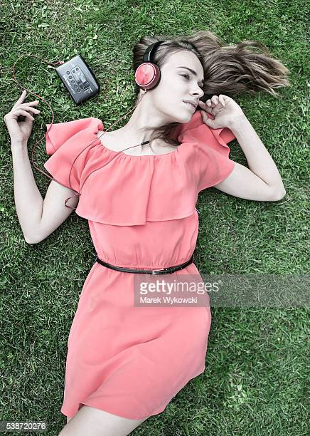 Young woman lying on the lawn in park and listening to music on a walkman.