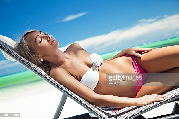 young woman lying on the lounge chair - hot blonde woman stock pictures, royalty-free photos & images