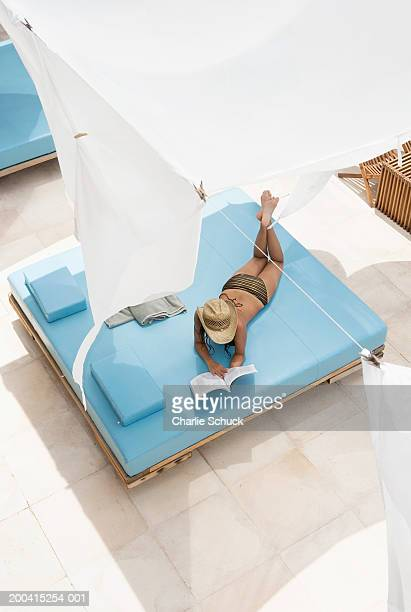 Young woman lying under sun tent reading, elevated view