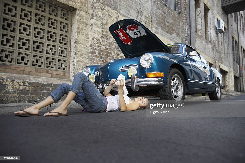 Young Woman Lying Underneath a Classic Car Cleaning a Tool : Stock Photo