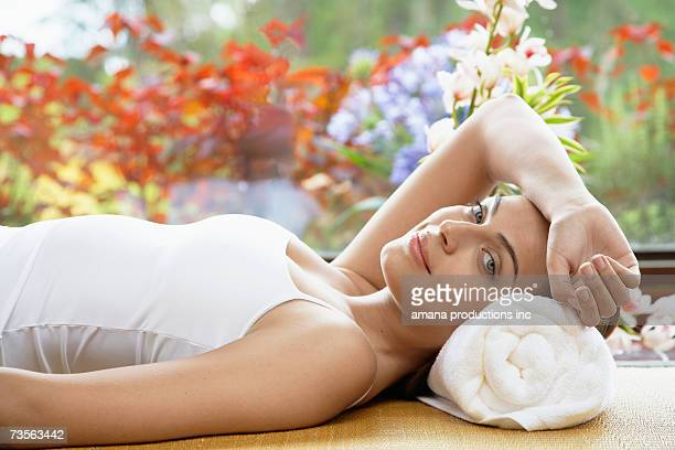 young woman lying with head on rolled towel, portrait - donna mutande foto e immagini stock