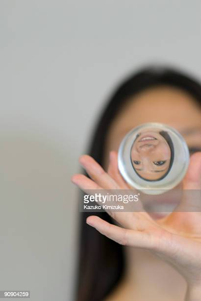 young woman magnifying her face - kazuko kimizuka stock-fotos und bilder