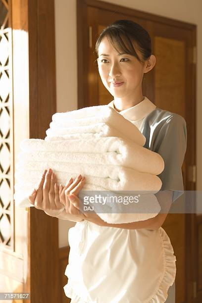 Young woman maid carrying towels, side view