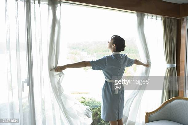 Young woman maid opening curtains, rear view