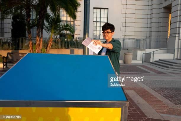 young woman mailing her ballot at the official pasadean ballot drop box - pasadena california stock pictures, royalty-free photos & images