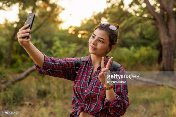 Young woman make selfie in forest