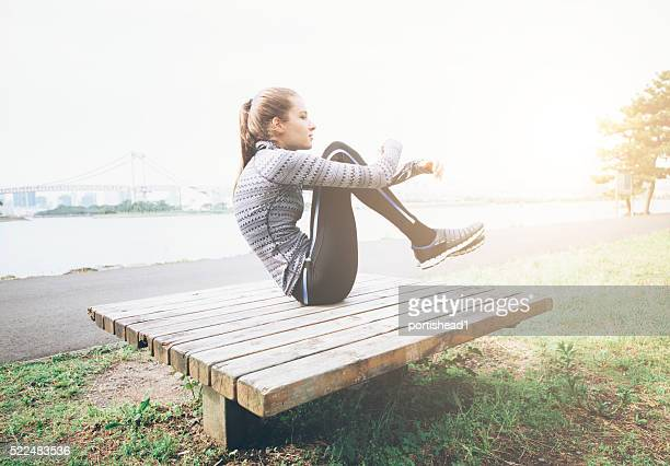 Young woman makes crunches outdoor