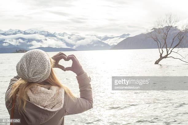 Young woman makes heart shape finger frame on lake Wanaka