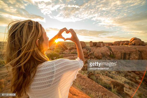 young woman makes heart shape finger frame to spectacular landscape-sunrise - australien stock-fotos und bilder