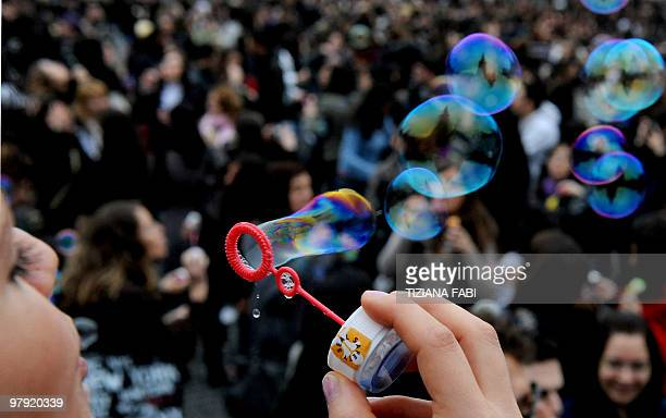 A young woman makes soap bubbles in the air during a flash mob at Piazza del Popolo in central Rome on March 21 2010 to mark the first day of Spring...