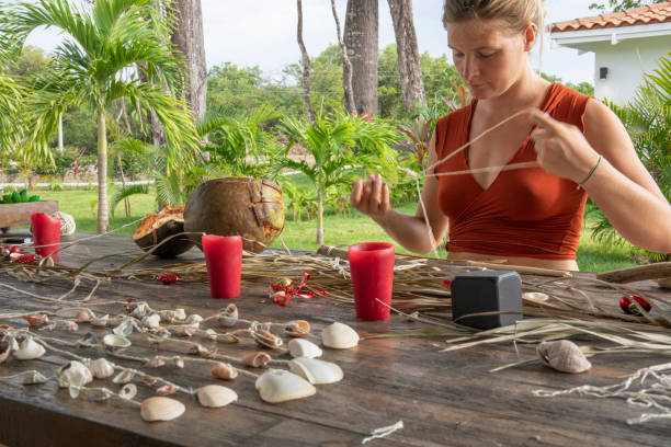 Young woman makes wind chimes in a tropical setting
