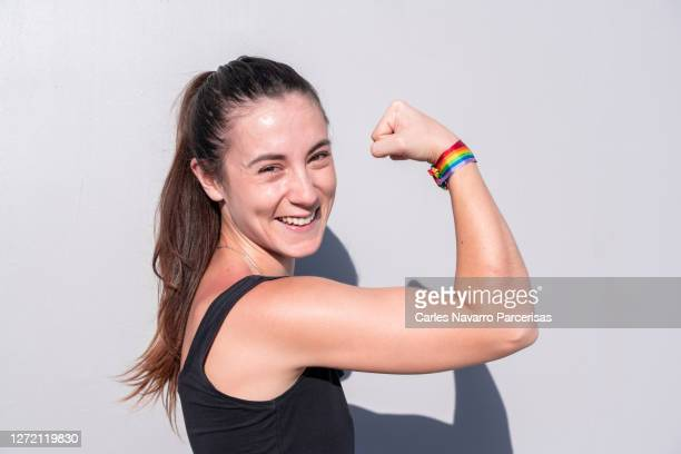 young woman making a gesture of strength with her arm carrying a rainbow flag bracelet in a white background in a sunny day - campaigner stock pictures, royalty-free photos & images