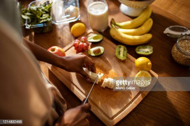 young woman making a healthy meal at home - fruit exotique photos et images de collection