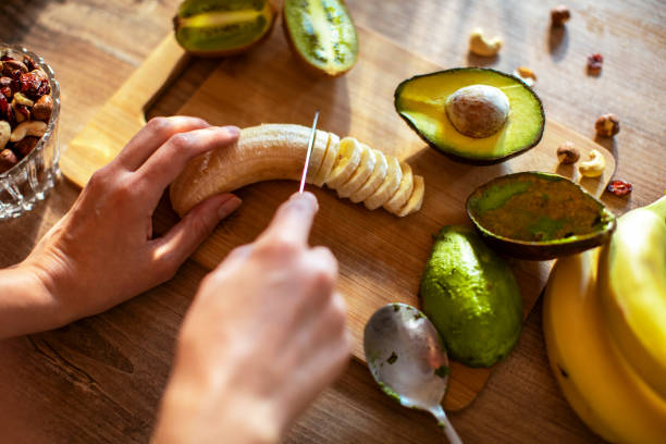 young woman making a healthy smoothie - banana and avocado stock pictures, royalty-free photos & images