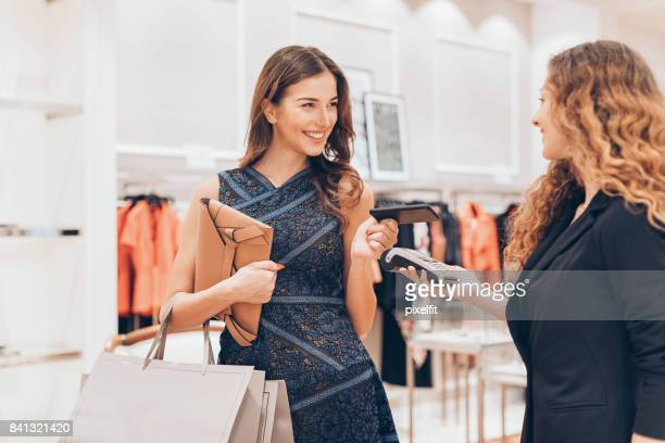 young woman making a payment in a luxury fashion store - luxury girl stock photos and pictures