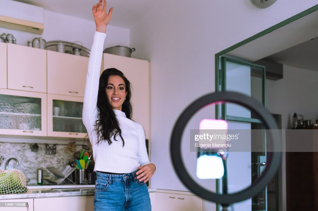 Young woman making a video at home, using mobile phone and ring light : Stock Photo