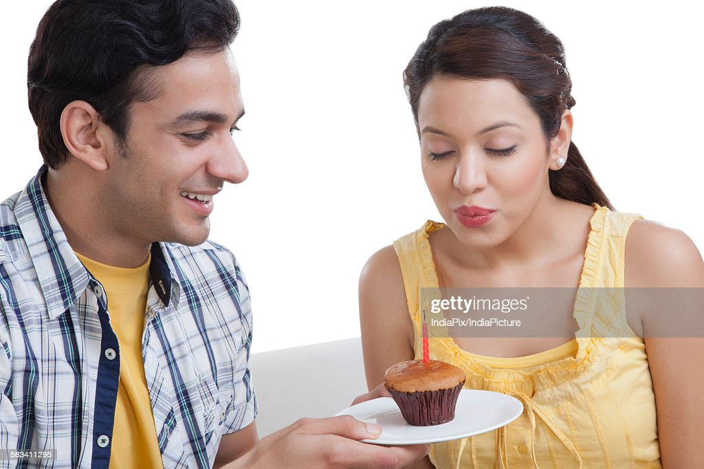 Young woman making a wish before blowing out candle : Stock Photo