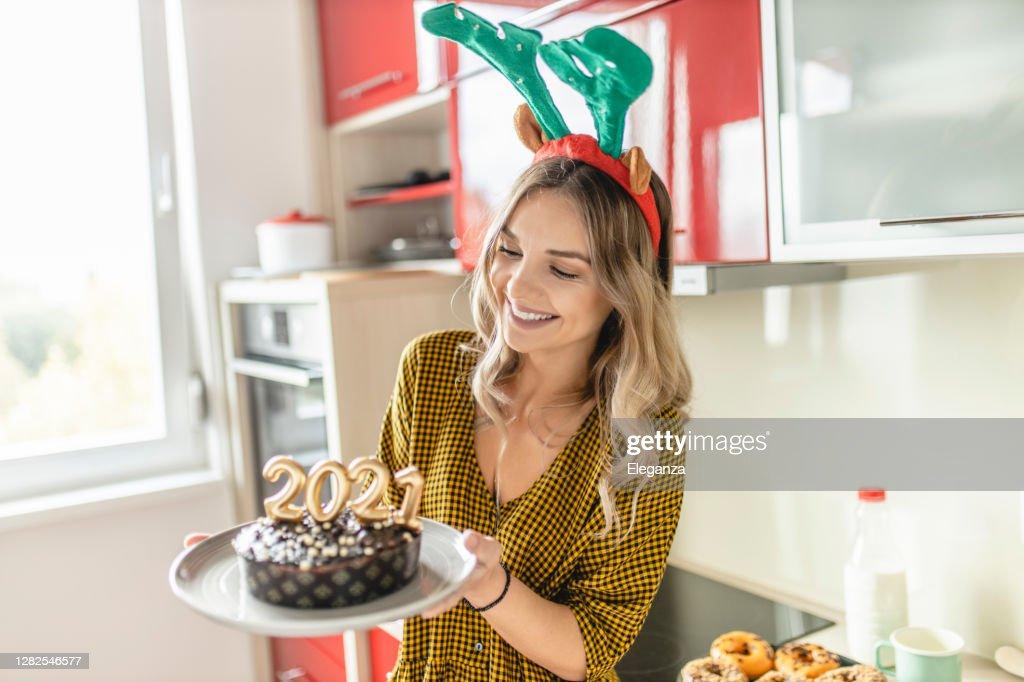 Jonge vrouw die chocoladecake met aangestoken kaarsen maakt en verfraait die als aantallen 2021 voor de partij van Het Nieuwe Jaar worden gevormd : Stockfoto