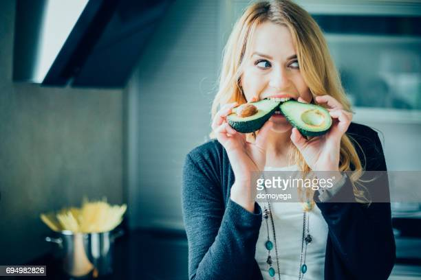 young woman making avocado meal in the kitchen - guacamole stock photos and pictures