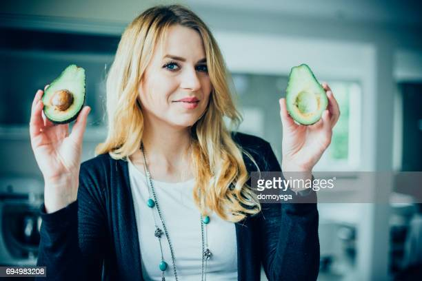 young woman making avocado meal in the kitchen - nutritionist stock pictures, royalty-free photos & images