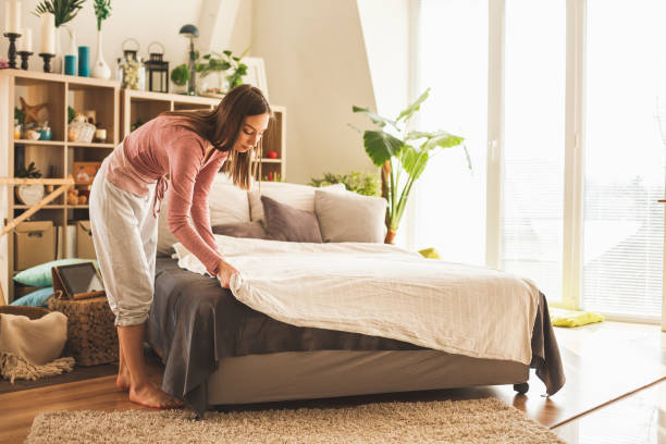 young woman making bed at home - preparation stock pictures, royalty-free photos & images