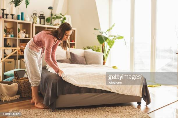 young woman making bed at home - bed stock pictures, royalty-free photos & images