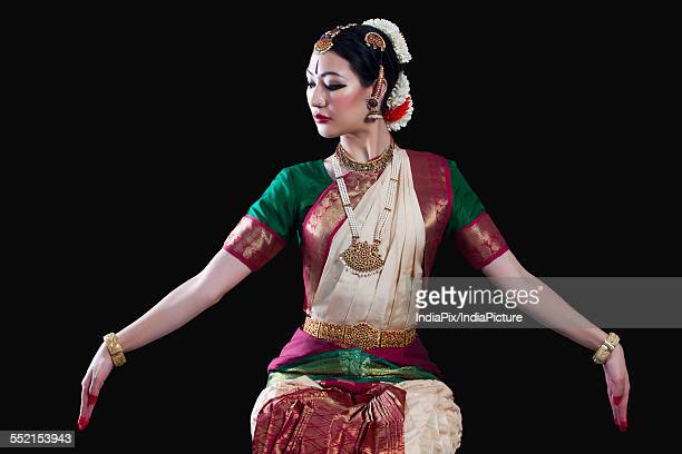Young woman making Bharatanatyam gesture called Dola-Hastam on black background