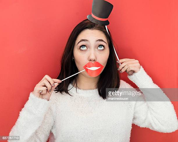 "young woman making faces with props on red wall. - ""martine doucet"" or martinedoucet stock pictures, royalty-free photos & images"