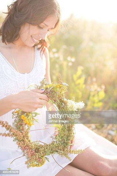 Young woman making flower wreath