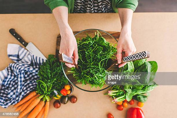 Young woman making fresh salad