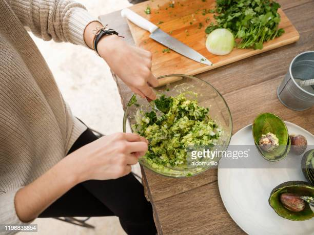 young woman making guacamole - guacamole stock pictures, royalty-free photos & images