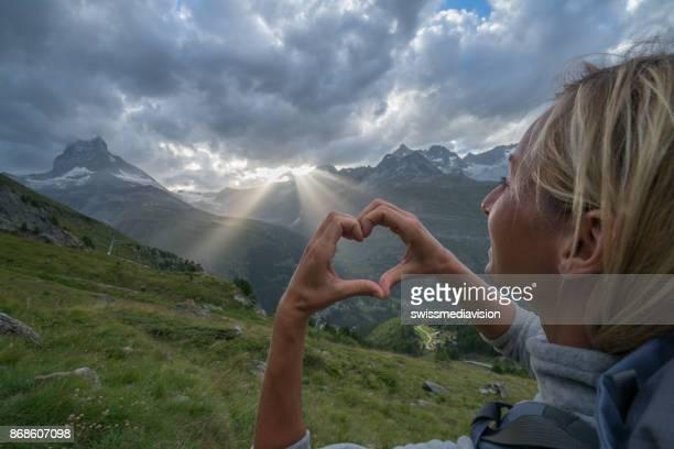 young woman making heart on matterhorn, switzerland - pinnacle peak stock pictures, royalty-free photos & images