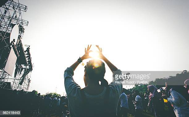 young woman making heart shape against sun - entertainment event stock pictures, royalty-free photos & images