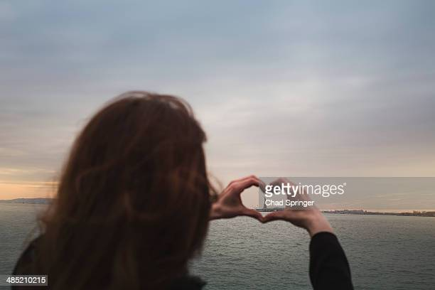 Young woman making heart shape around statue of liberty, New York, USA