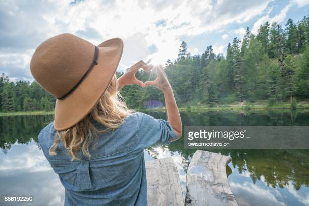 Young woman making heart shape finger frame in nature